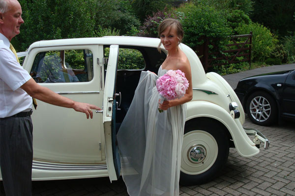 Bride traveling in style in Vintage Triumph wedding car